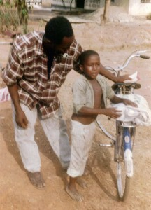 fioh.fund.sierra.leone.post.war.reconstruction. Eddie Kargbo giving a bicycle to a boy whose father was killed in the civil conflict